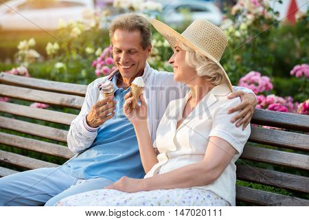 Couple with ice cream smiling. Adult man hugs lady. Pleasant conversation with friend. Romance of summer.