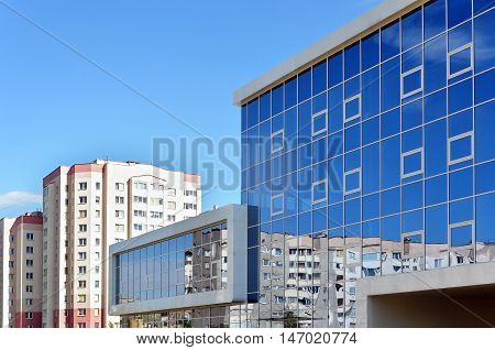 Grodno, Belarus - August 8, 2016: A modern rectangular building in a residential area made of white panels and mirrored glass walls reflecting the blue sky. Grodno Belarus.