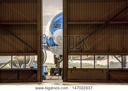 Airplane In Front Of Half Opened Door To Hangar