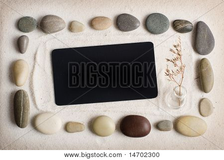 Sea stones and black cut-away on sand.
