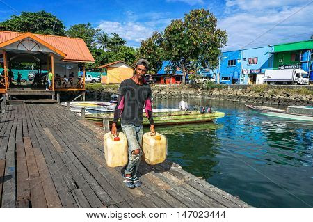 Semporna,Sabah-Sep 10,2016:Boatman with gallons petrol ready to island at Semporna jetty.Its a gateway for vacation,diving & snorkeling trips to the islands of Sipadan,Mabul,Mataking,Maiga & others