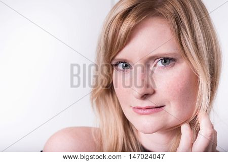 beautiful blonde woman is looking strictly into camera