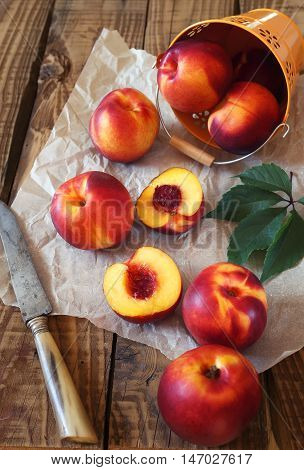 Fresh ripe nectarines on wooden table, intact and halves