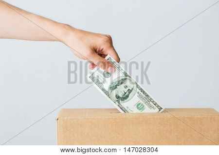 charity, finances, funding, investment and people concept - male hand putting dollar money into donation box