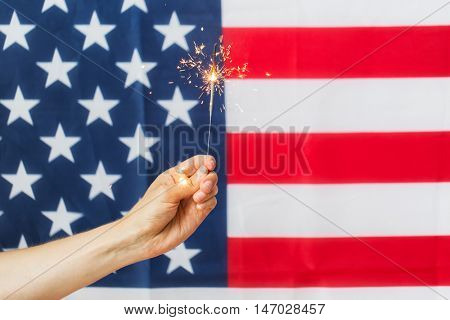 american independence day, patriotism, holidays and people concept - close up of hand holding sparkler over national flag