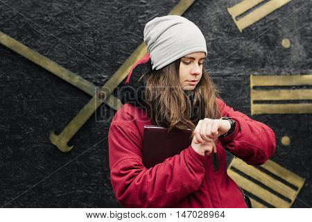 Beautiful white girl is waiting for someone outdoor she is looking at her watch. Big roman numeral clock on the background