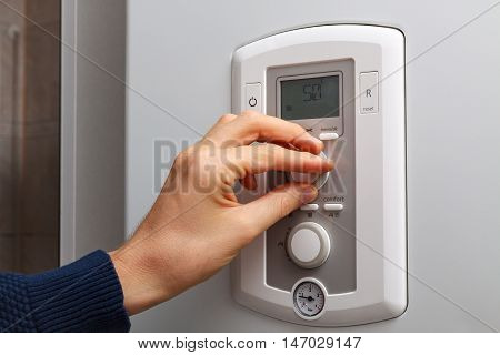 Men hand regulate temperature on 50 degree in control panel of central heating.