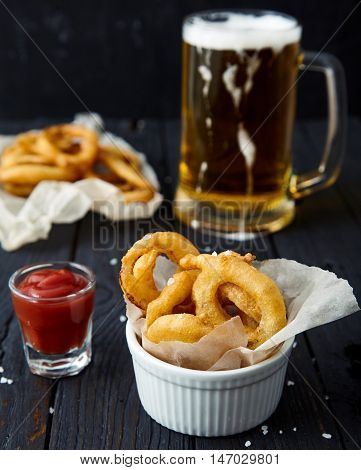 Appetizing, crispy, golden onion rings sprinkled with sea salt in a white bowl with paper, ketchup shot and cup of salt next to it. Behind blurred beer mug. Delicious snack on dark wood background