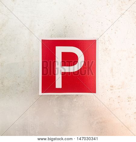 Red an white parking area sign on metallic background.