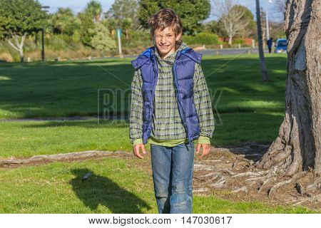 young happy smiling boy walking in park, auckland, new zealand