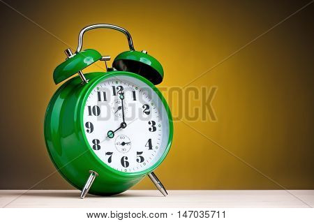 Retro alarm clock on yellow background. Green alarm-clock old style on wooden table.