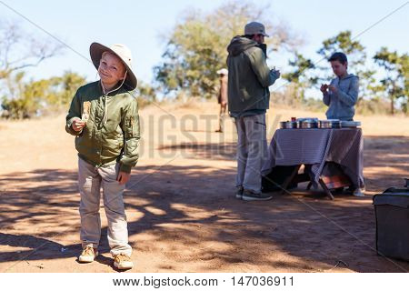 Family of father and kids on African safari vacation enjoying bush breakfast