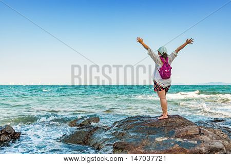Happy young woman spreading hand on the rock beach for relaxing.