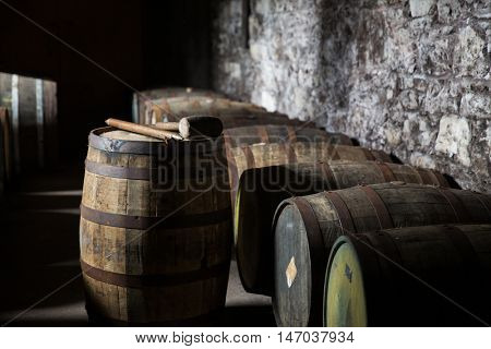 storage, container, winery, brewery and object concept - close up of old wooden barrel in wine cellar