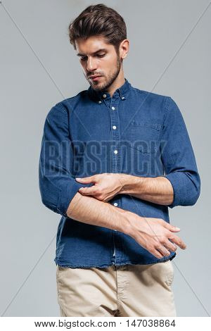Portrait of a handsome serious man tacking sleeves isolated on the gray background