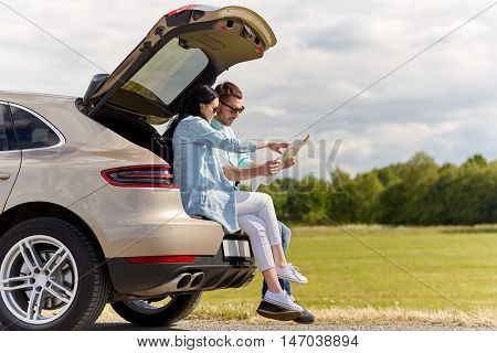 leisure, road trip, travel and people concept - happy man and woman searching location on map sitting on trunk of hatchback car outdoors