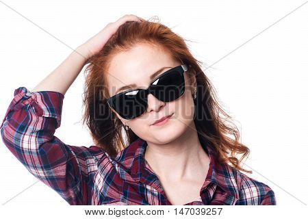 Beautiful girl in sunglasses. Close-up portrait of a young woman in a checkered shirt isolated on a white background