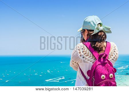 Young woman is taking a sea photo on clear sky day.