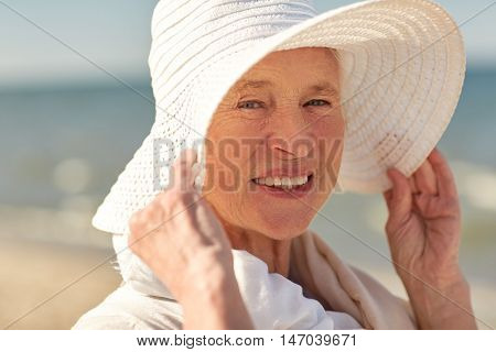 age, leisure, travel, tourism and people concept - close up of happy senior woman in sun hat on summer beach