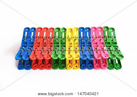 Multicoloured plastic clothes pegs on a white background.