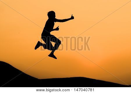 silhouette of man in happy jumping and thump up on orange sunset sky