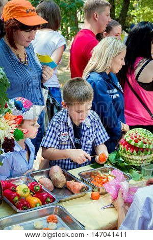 Zaporizhia/Ukraine- September  3, 2016: Charity festival for children - City of professions . Boy participating at fruits and vegetables carving workshop, making carrot flower - food decoration
