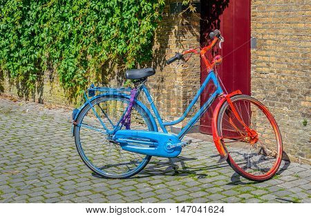 Parked ladies bike painted in red and blue colors and closed with a purple wrapped chain lock.