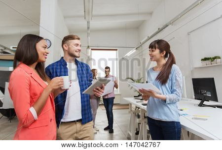 business, communication, startup and people concept - happy multiracial creative team or students with tablet pc and papers on coffee break talking at office