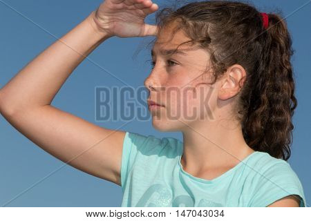 Young Girl Looking Ahead With The Hand In Forehead