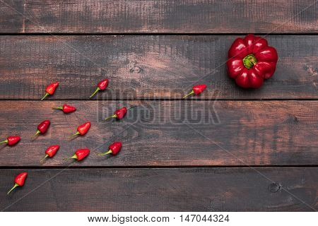 fresh bitter and sweet pepper on wooden background