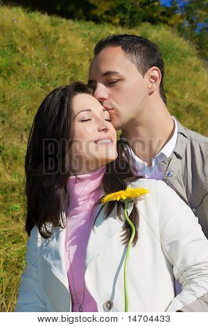 Young man kissing his girlfriend standing outside