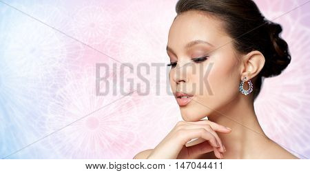 beauty, jewelry, accessories, people and luxury concept - close up of beautiful asian woman face with earring over rose quartz and serenity patterned background