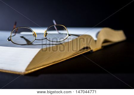 Book with reading glasses on top - a person is currently reading for pleasure studying or researching