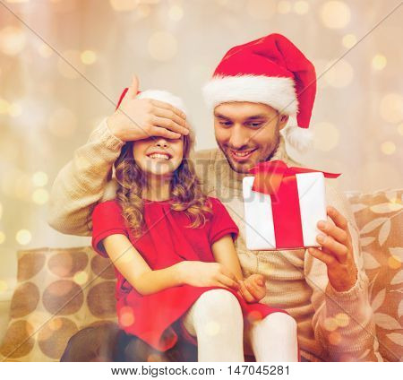family, christmas, x-mas, winter, happiness and people concept - smiling father surprise daughter with gift box covering eyes with hand