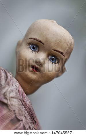 Face of an old porcelain doll in a flea market