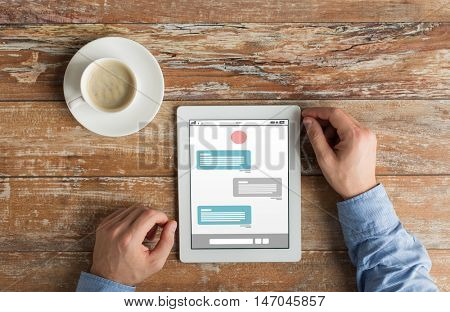 business, online communication, people and technology concept - close up of male hands with messenger on tablet pc computer screen and coffee cup on wooden table