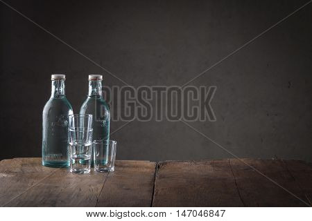 Two bottles of beverage on a rustic counter top with a stack of clean glasses or tumblers and copy space to the side on a dark background