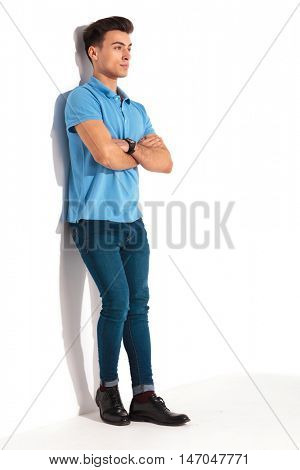 full body picture of a young casual man in blue polo shirt, leaning against studio wall with hands crossed and looking away from the camera