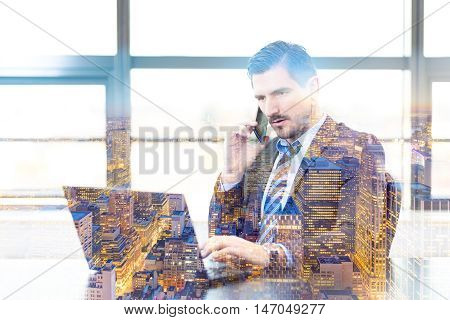 Portrait of successful corporate businessman in modern office focused on data on his laptop computer while talking on mobile phone. New Your city lights reflection in window. Business concept.
