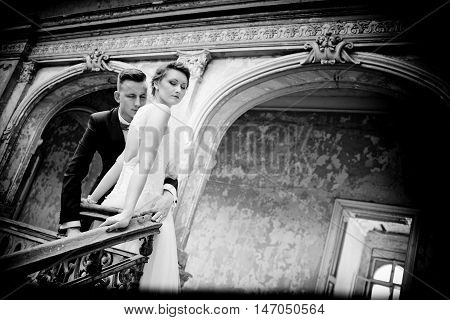 Newlyweds Kissing Near Old Stairs