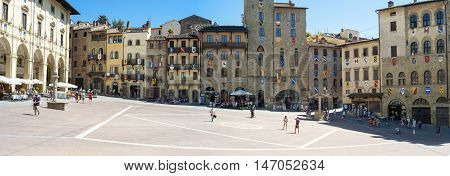AREZZO, ITALY - AUGUST 16, 2016: panoramic wide angle view of Piazza Grande, the main square in the medieval city centre of Arezzo (Tuscany, Italy).