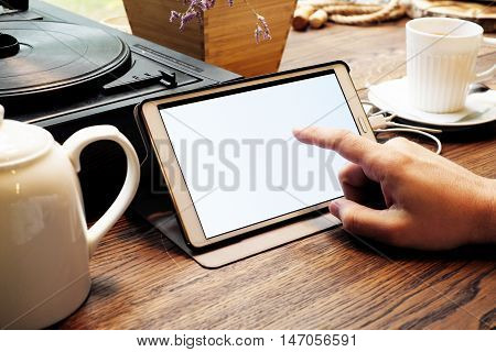 Tablet computer empty screen in man hands. Reading charts document in cafe. Business man working out of office.