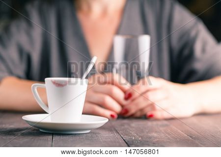 Cup Of Coffee On A Wooden Table With Glass Of Water In Woman Hands