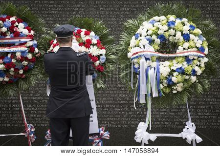 NEW YORK - SEPT 9 2016: A man adjusts one of the ceremonial wreaths placed for the 9/11 Memorial Commemoration Service at the NYC Police Memorial on the 15th anniversary of the terror attacks.