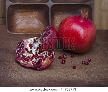 Red ripe pomegranates on old wooden board