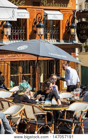 Paris France - July 06 2016: A traditional restaurant in Paris in the Butte Montmartre. Parisians and tourists enjoy food and drinks under the sun. Montmartre area is most popular destinations in Paris has lots of cozy cafes restaurants bistros night club