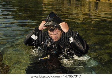 Side mount diver putting on a hood before diving