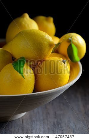 Fresh lemons with leaves in plate, close up