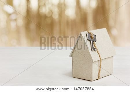 Model of cardboard house with key against bokeh background. House building, loan, real estate or buying a new home concept.
