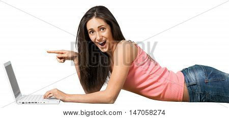 Young woman lying down in front of a laptop and pointing at the screen